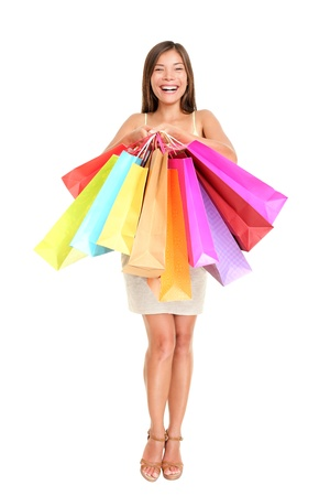 Shopper woman holding shopping bags standing happy smiling and excited in full body isolated on white background.