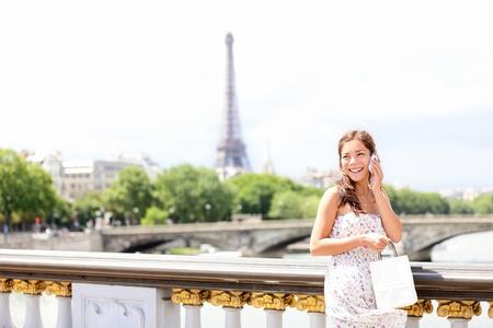 calling: Par�s, una mujer hablando por tel�fono m�vil  tel�fono inteligente en Par�s, Francia, con la Torre Eiffel en el fondo.