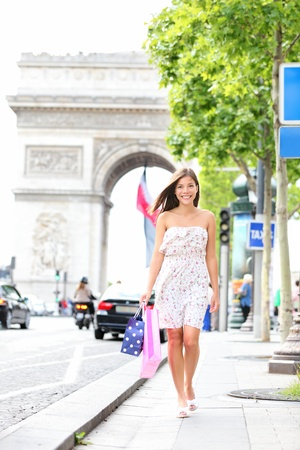 Paris woman shopping walking on Champs-Elysees with Arc de Triomphe in the background.