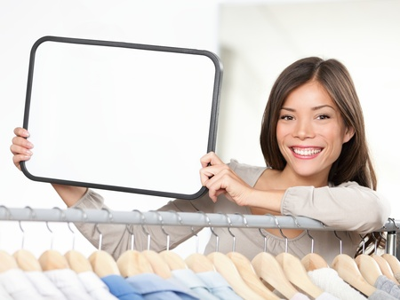 seller: Shop sign woman. Small retail business owner showing blank sign in clothing store. For shopping or sale copy.  Stock Photo