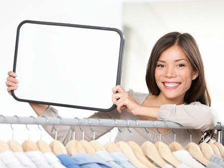 Uithangbord vrouw. Kleine detailhandel ondernemer toont leeg bord in de kledingwinkel. Om te winkelen of verkoop kopie. Stockfoto