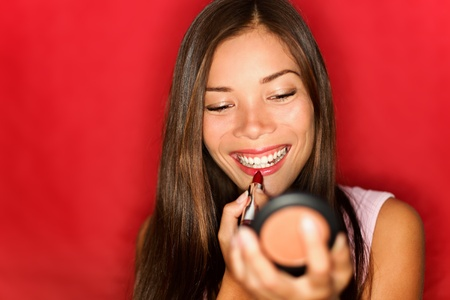 putting on: Woman putting makeup lipstick. Asian girl putting lip gloss red lipstick smiling happy looking in pocket mirror.