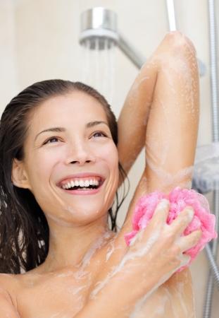 axila: Proyección asiática joven lavando su axila sonriendo feliz.