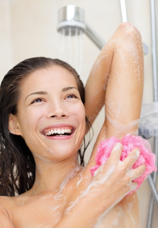 Young asian showing washing her armpit smiling happy.  Stock Photo