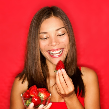 woman eating strawberry smiling happy on red background. photo