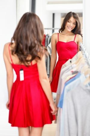 Frau, die versucht roten Kleid Einkaufsmöglichkeiten für Bekleidung.