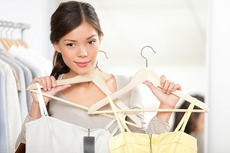 changing clothes: Mujer de compras tratando de ropa. La mujer de elegir entre vestidos de verano que buscan en el espejo. Foto de archivo