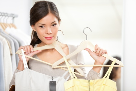 changing clothes: shopping woman trying clothes. Woman choosing between summer dresses looking in mirror.
