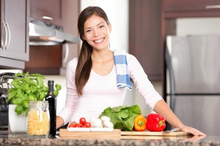 Küche Frau, die gesundes Essen stehend glücklich lächelnd in Küche und bereitet Salat.