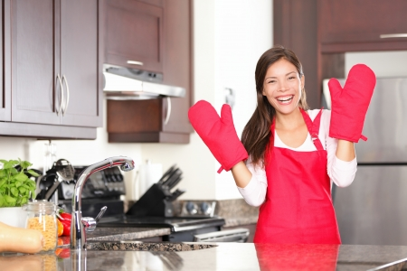 Happy baking cooking woman standing in her new kitchen smiling cheerful wearing apron and oven mitts ready to bake.