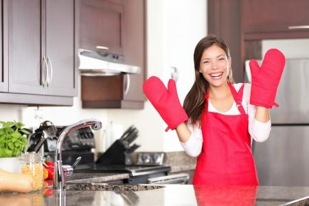 panettiere: Felice donna cottura cottura in piedi nella sua nuova cucina sorridendo allegra indossare grembiule e guanti da forno pronti a cuocere.