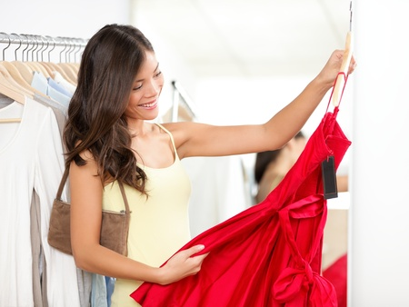Woman shopping for dress in clothing retail store. photo