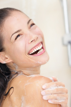 Happy smiling asian woman washing shoulder showering in bathroom. photo