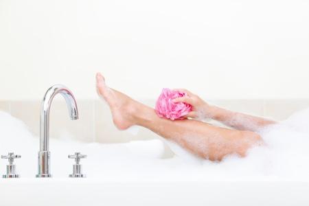 Woman in bath washing leg in bathtub with a lot of bubble bath foam.