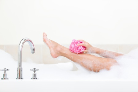 Woman in bath washing leg in bathtub with a lot of bubble bath foam.