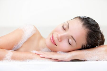 woman relaxing in bath with serene smile and closed eyes full of bath foam.
