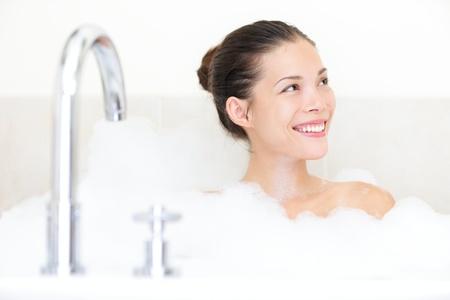 Bad mit Badewanne Frau genießen Badeschaum lächelt glücklich.
