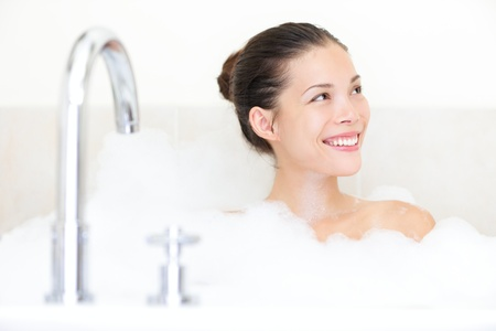 bathtub: Bath woman enjoying bathtub with bath foam smiling happy.  Stock Photo