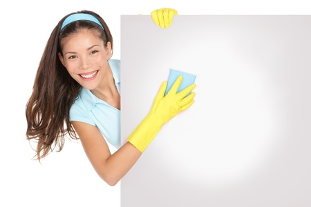 Cleaning woman holding showing billboard sign  Cleaning lady holding and cleaning blank empty billboard paper sign  Cute funny image of cleaning woman wearing yellow rubber gloves smiling happy  Mixed ethnicity Caucasian   Chinese Asian female model isola photo