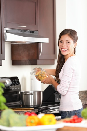 Woman in kitchen making food in kitchen  Happy smiling young woman preparing pasta dinner in her new kitchen  Beautiful young mixed race Caucasian   Chinese Asian female model at home  photo