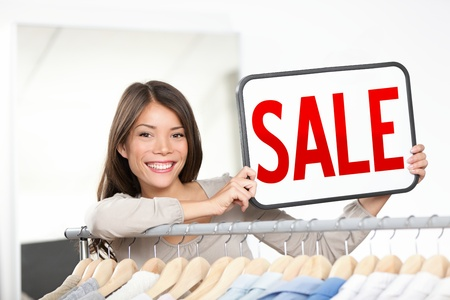 Ladenbesitzer Frau Verkauf unterzeichnen Kleine Bekleidungskette Ladenbesitzer zeigt rot sale sign glücklich lächelnde hinter Kleiderständer Junge weibliche professionelle Unternehmer in ihrem kleinen Laden Mixed Rennen chinesischen asiatischen kaukasischen Frau Unternehmer Lizenzfreie Bilder