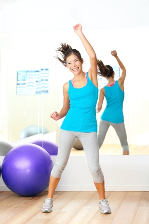 Gym aerobics zumba fitness dance instructor. Woman dancing happy in fitness center. Young beautiful mixed race Caucasian / Chinese Asian female fitness model. photo