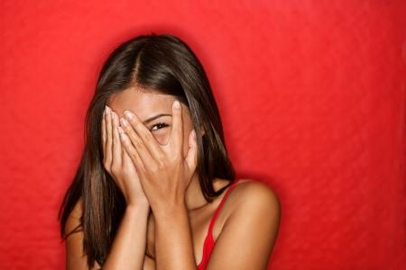 expresiones faciales: Juguet�n mujer t�mida esconde t�mido rostro sonriente. Lindo china asi�tica  cauc�sica mujer sonriendo feliz a trav�s de las manos. Fondo rojo.