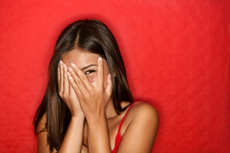 Playful shy woman hiding face laughing timid. Cute Chinese Asian  Caucasian woman smiling happy through hands. Red background. Stock Photo