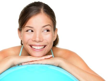 Gym pilates vrouw op zoek naar de kant met iets. Mooie jonge gezonde levensstijl vrouw die ontspannen op pilates oefening bal na de training. Gemengd ras fitness-model op een witte achtergrond. Stockfoto