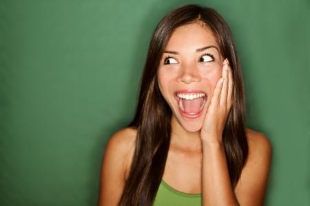 Erstaunen - eine Frau aufgeregt zur Seite schauen. Überrascht glückliche junge Frau Blick von der Seite in Aufregung. Mixed Rennen chinesischen asiatischen  weißen kaukasischen weiblichen Modells auf grünem Hintergrund.