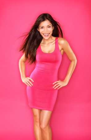 Mooie Aziatische vrouw model portret in warm roze jurk op roze achtergrond lachende fris, energiek en gelukkig. Gorgeous gemengd ras Kaukasisch  Aziatisch Chinese vrouwelijke fashion model brunette.