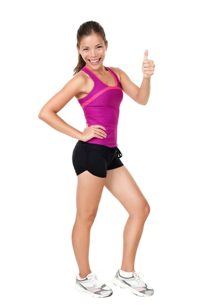 Fitness woman showing thumbs up success sign standing in running fitness outfit in full body isolated on white background. Fresh healthy lifestyle concept image of happy young mixed race Chinese Asian / white Caucasian female fitness model.