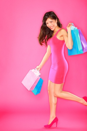 Shopping lady. Woman shopper holding shopping bags walking smiling happy and joyful in full length on pink background. Young beautiful mixed race Asian  Caucasian female fashion model. Stock Photo