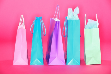 Shopping bags on pink background. Many colorful shopping paper bags standing on pink floor. photo