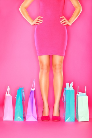 consumerism: Shopping. Shopping bags and legs of woman shopper on pink background. Sale, Shopping, Fashion or consumerism concept with shopaholic in high heels shoes.