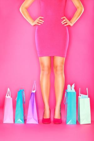 шопоголика: Shopping. Мешки и ноги женщины покупателя на розовом фоне. Продажа, Покупки, Мода и потребительство концепции с шопоголика в туфли на каблуках.