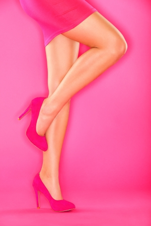 Pink high heels shoes and sexy woman legs in pink skirt on pink background. Beautiful female legs and shoes. photo