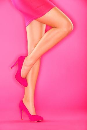 Rosa High Heels Schuhe und sexy Frau Beine in rosa Rock auf rosa Hintergrund. Schöne weibliche Beine und Schuhe.