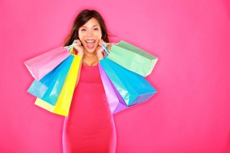 Einkaufen Frau glücklich aufgeregt und fröhlich halten Einkaufstüten zeigt frische energetische Lächeln auf rosa Hintergrund. Schöne glücklich lächelnde multirassischen Kaukasier  chinesischen asiatischen brunette Mode-Modell.