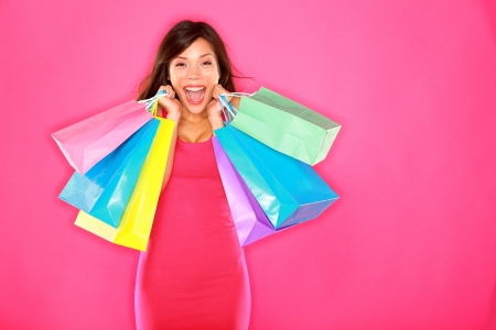 Shopping woman happy excited and cheerful holding shopping bags showing fresh energetic smile on pink background. Beautiful smiling happy multiracial Caucasian  Chinese Asian brunette fashion model.