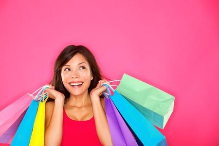 Einkaufen Frau mit Einkaufstüten suchen bis zu der Seite, auf rosa Hintergrund auf Kopie Raum. Schöne junge gemischte Rasse Europäisch  chinesische asiatische Einkäufer lächeln glücklich.