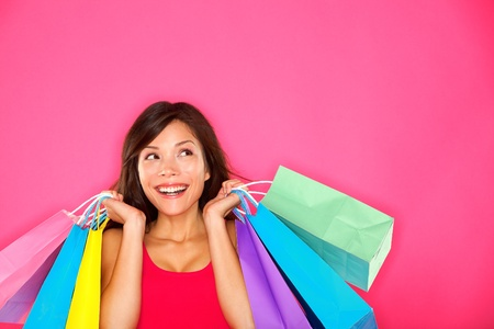 happy shopping: Shopping woman holding shopping bags looking up to the side on pink background at copy space. Beautiful young mixed race Caucasian  Chinese Asian shopper smiling happy.