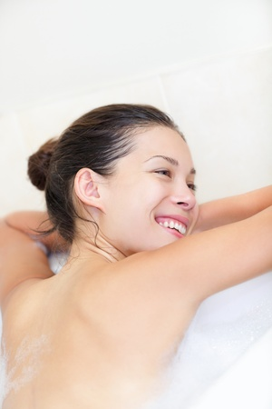 Woman in bath relaxing smiling happy resting on towel. Beautiful young mixed race woman bathing in bathtub. photo