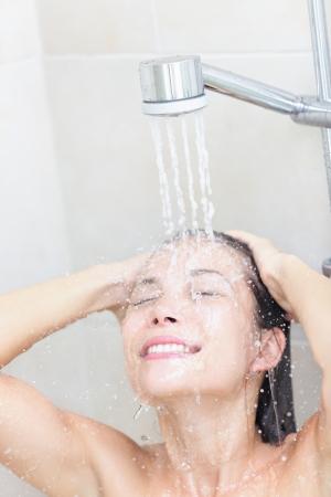 cabine de douche: Douche femme se laver le visage et les cheveux douche sourire heureux sous la tête de douche. Belle jeune joyeuse mixte modèle féminin course en salle de bains à la maison. Banque d'images