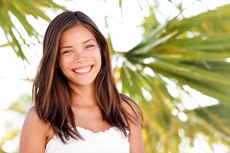 mixed race ethnicity: Multiracial summer woman portrait  Ethnic mixed Asian   Caucasian woman smiling happy on beach tanned and fresh looking at camera joyful  Youthful girl in her 20s  Stock Photo
