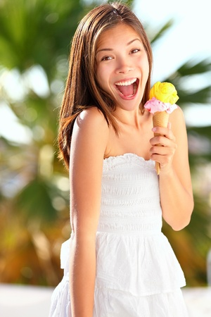helados: Ice Cream Girl emocionada y feliz comiendo cono de helado en la playa durante las vacaciones de verano precioso dulce mestiza asi�tica mujer china de raza cauc�sica joven fuera