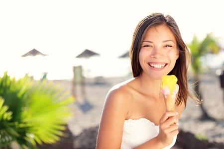 Kvinna äta glass ute på sommarsemester i Holiday Beach Resort Glad blandad ras flicka i tjugoårsåldern