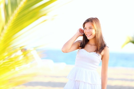 Summer girl on beach  Cute young woman model standing happy and lovely in white sundress on tropical beach  Adorable mixed race Asian   Caucasian eurasian woman in her twenties  Archivio Fotografico