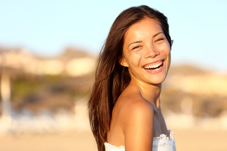 Summer woman portrait  Asian girl smiling happy laughing on beach vacation enjoying warm sunshine  Gorgeous mixed race Asian Chinese  Caucasian female model outside  Archivio Fotografico