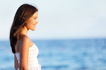 Young woman on beach smiling happy at sunset  Lovely sweet asian woman in her twenties enjoying view of ocean standing in white dress